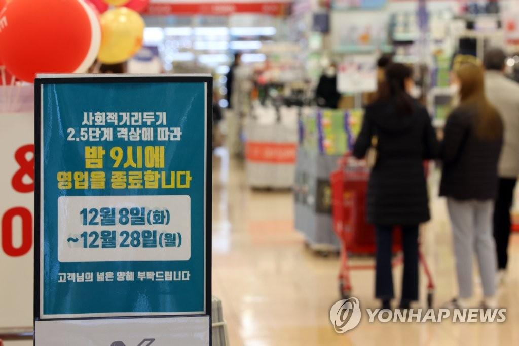 资料图片:12月8日,首尔市区一家大型超市摆出缩短营业时间的通知。韩国政府当天起将首都圈防疫响应级别上调至2.5级,首都圈大型超市须在晚9时停止营业。 韩联社