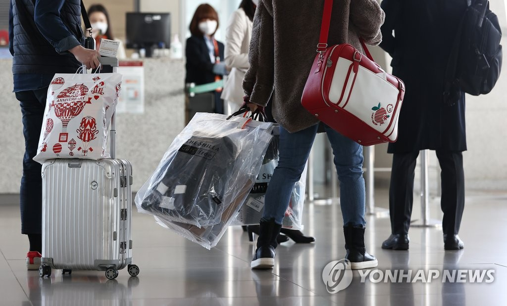 资料图片:2020年12月12日,在仁川国际机场,国际低空游的乘客正拿着购买的免税品进入登机口。 韩联社