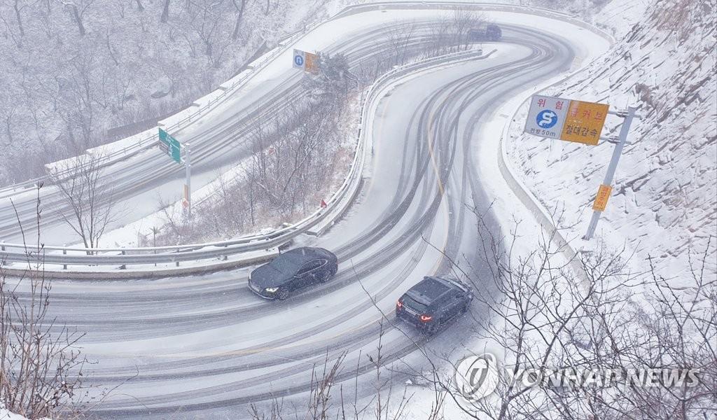 资料图片:12月13日,在江原道寒溪岭,车辆行驶在下过雪的路上。 韩联社/读者供图(图片严禁转载复制)