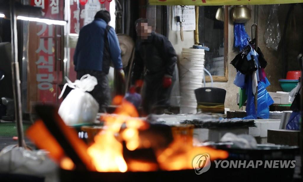 资料图片:12月14日上午,在首尔市区的一个市场,商人们在火炉边忙碌。 韩联社
