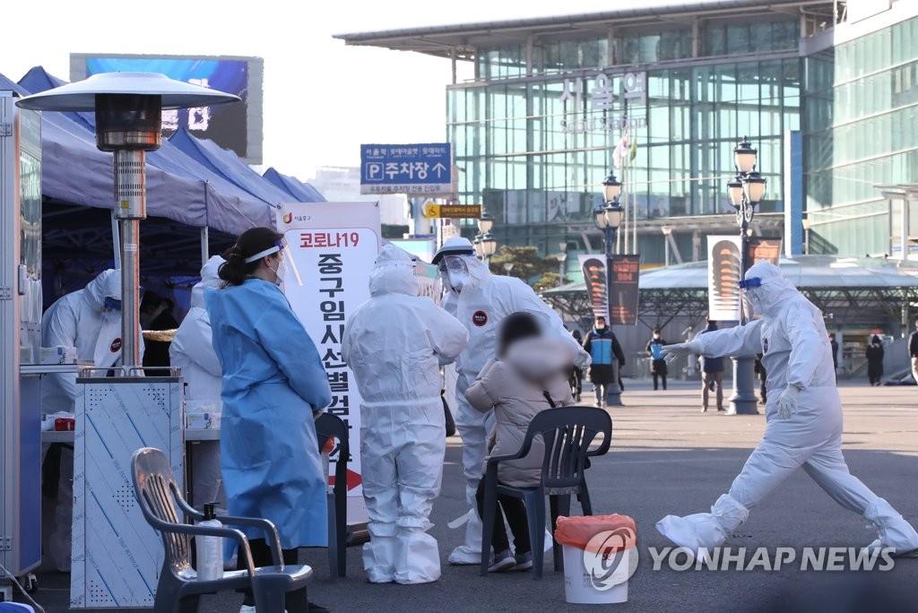 资料图片:12月14日,在首尔火车站前临时设置的筛查诊所,市民们正在接受病毒检测。 韩联社