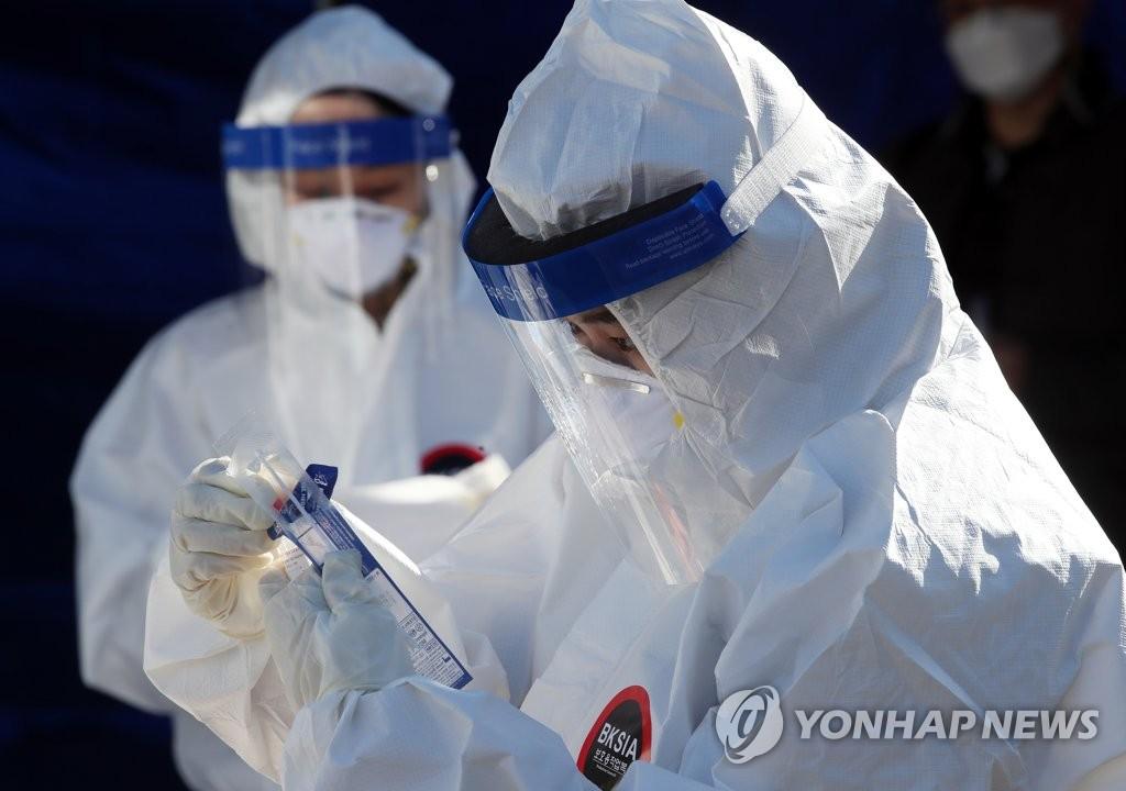 资料图片:医务人员冒着严寒抗疫。 韩联社