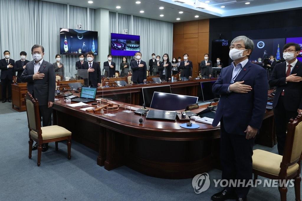 12月15日,在青瓦台,总统文在寅在主持国务会议前向国旗行礼。 韩联社