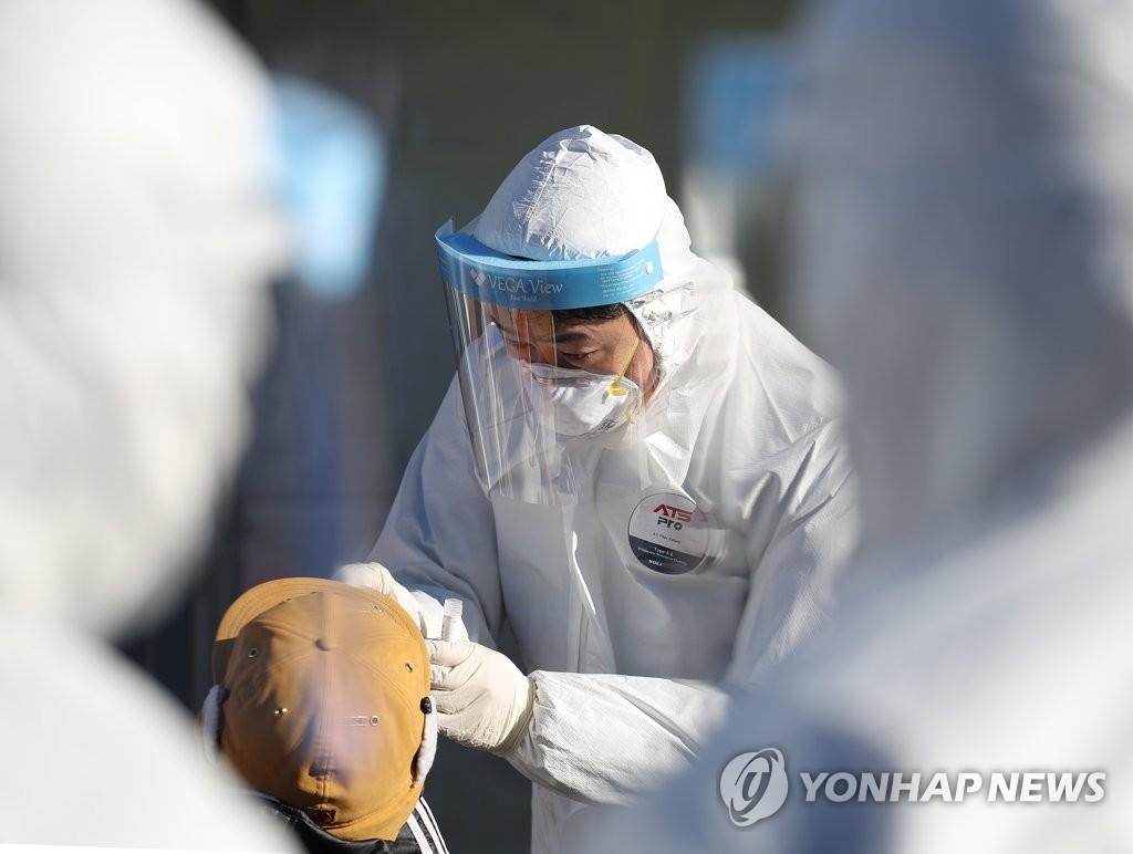 资料图片:给市民进行新冠病毒检测的医疗人员 韩联社
