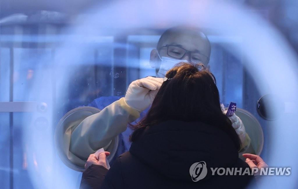 资料图片:12月21日,在设于首尔火车站广场的临时筛查诊所,医务人员采集市民鼻咽试子进行病毒检测。 韩联社