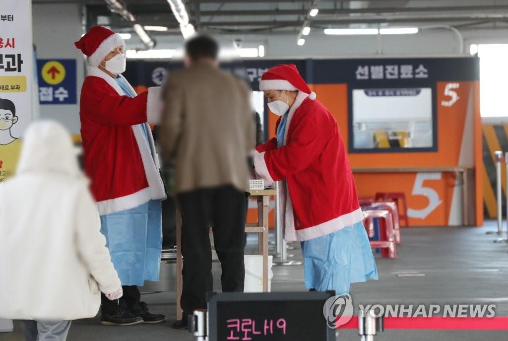 资料图片:12月24日,在位于光州市北区的一处筛查诊所,两位扮成圣诞老人的医护人员为市民进行病毒检测采样,疫情下仍不失节日气氛。 韩联社