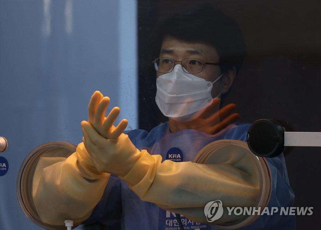 资料图片:12月25日,在设于首尔中区首尔火车站广场的筛查诊所,医务人员为采样做准备。 韩联社