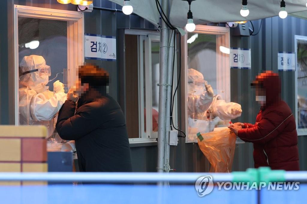 1月6日,在首尔站前的临时筛查诊所,医务人员正在采集样本。 韩联社