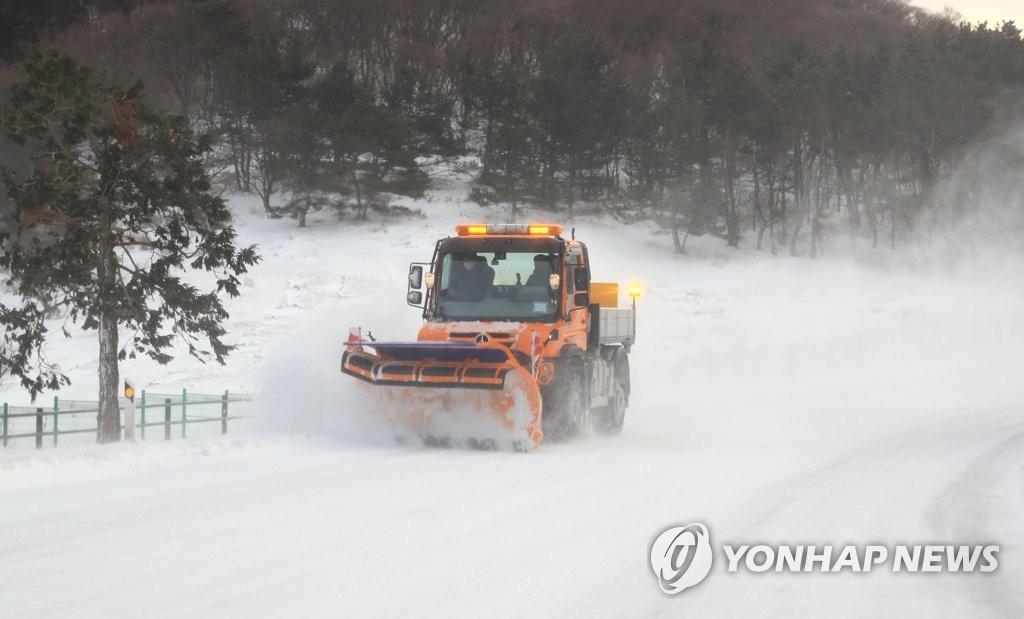 1月7日,在济州516道路上,一辆除雪车在清扫积雪。 韩联社