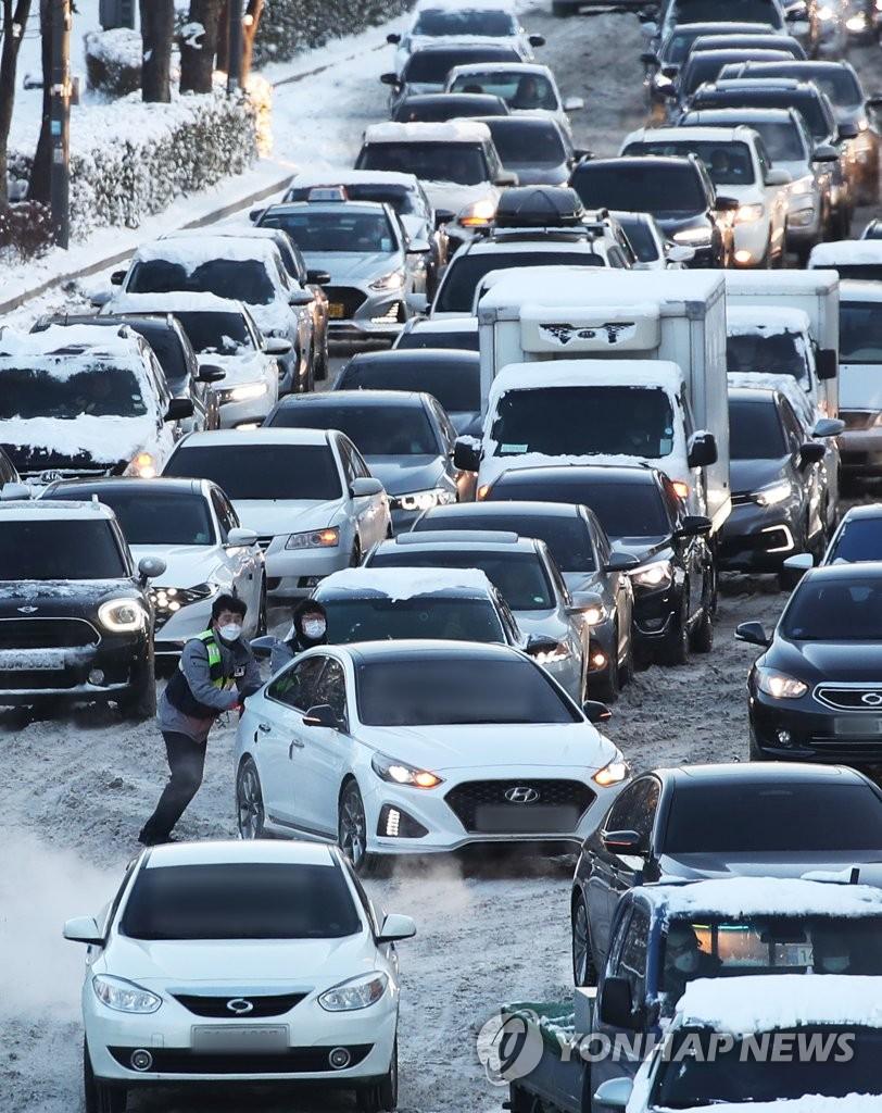 资料图片:1月7日上午,在京畿道水原市灵通区光教路一带,连夜强降雪导致早高峰交通严重受阻。图为交警在雪路上推出被困车辆。 韩联社