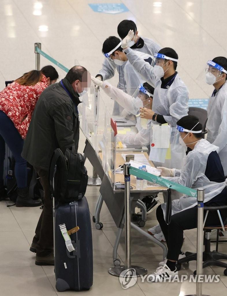 资料图片:1月7日,在仁川机场,工作人员向抵达乘客说明入境流程。 韩联社