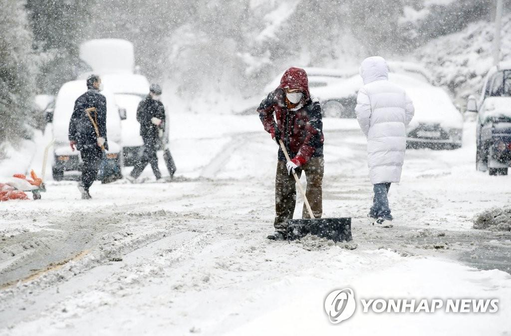 1月7日,在光州北区云岩3洞的一条道路上,工作人员清扫路上的积雪。 韩联社/光州北区政府供图(图片严禁转载复制)