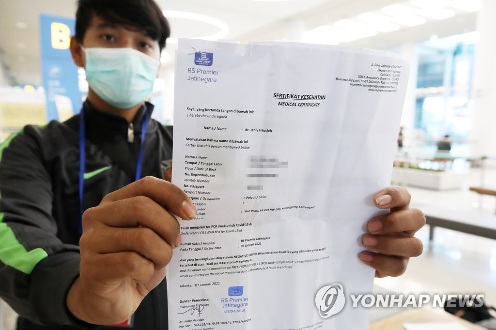 资料图片:1月8日,在仁川机场第二航站楼,一名来自印度尼西亚的入境人员出示核酸检测(PCR)阴性证明。 韩联社