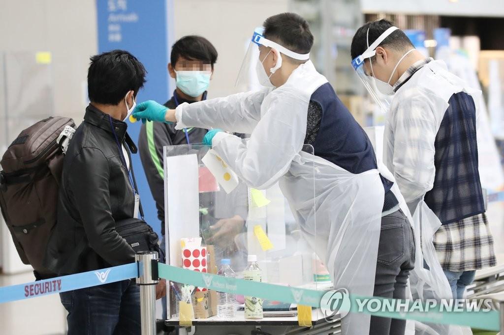 资料图片:1月8日,在仁川国际机场第二航站楼,防疫人员为入境者贴检测贴纸。 韩联社