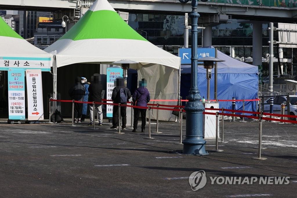 资料图片:1月9日,在设于首尔站的临时筛查诊所,市民排队接受病毒检测。 韩联社