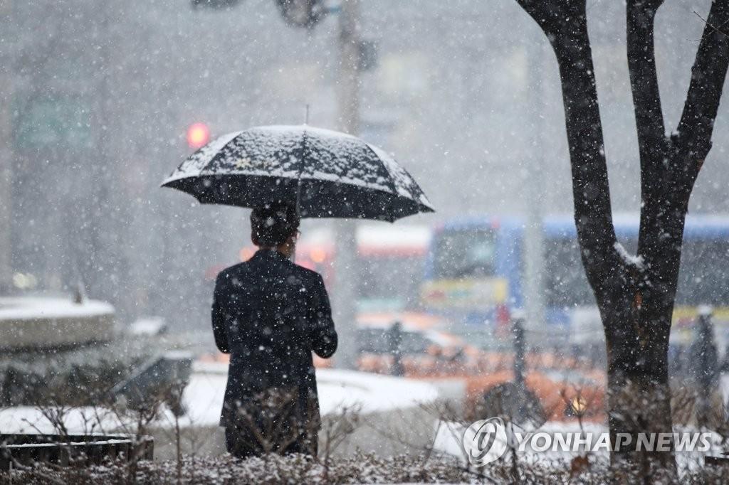 资料图片:1月12日,在首尔市中区明洞一带,市民撑伞走在雪中。 韩联社