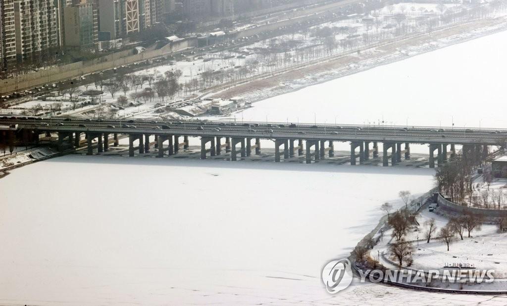 资料图片:1月13日,从首尔汝矣岛63大厦上眺望,整条汉江被白雪覆盖。 韩联社