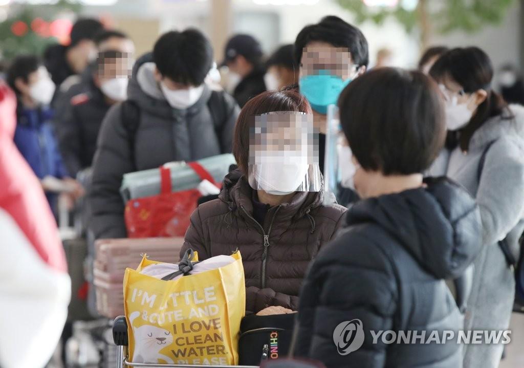 资料图片:1月14日,在仁川国际机场第一航站楼,前往中国烟台的旅客排队办理出境手续。 韩联社