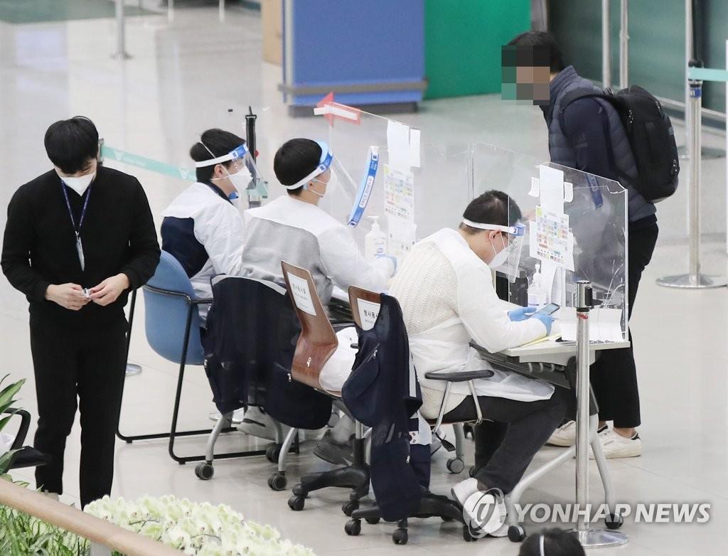 资料图片:1月14日,在仁川国际机场第一航站楼,防疫人员向入境人员介绍病毒检测流程。 韩联社