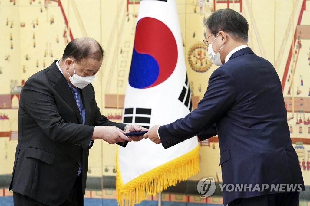资料图片:总统文在寅向韩国新任驻日大使姜昌一(左)授予国书。 韩联社