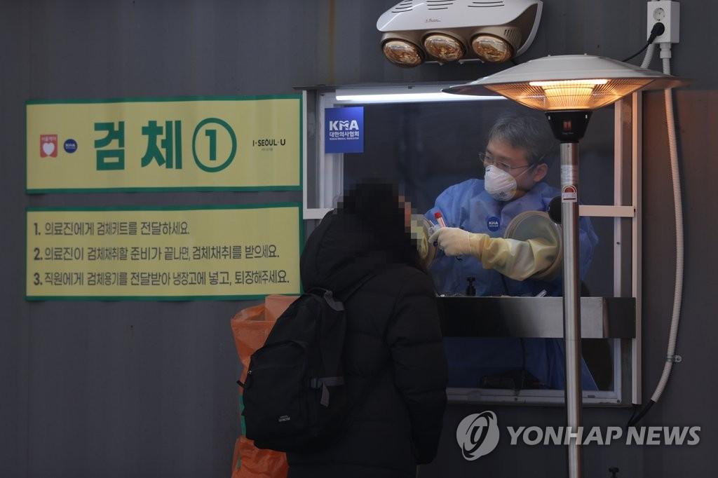 资料图片:1月15日,在位于首尔广场的临时筛查诊所,一市民正在接受新冠病毒检测。 韩联社