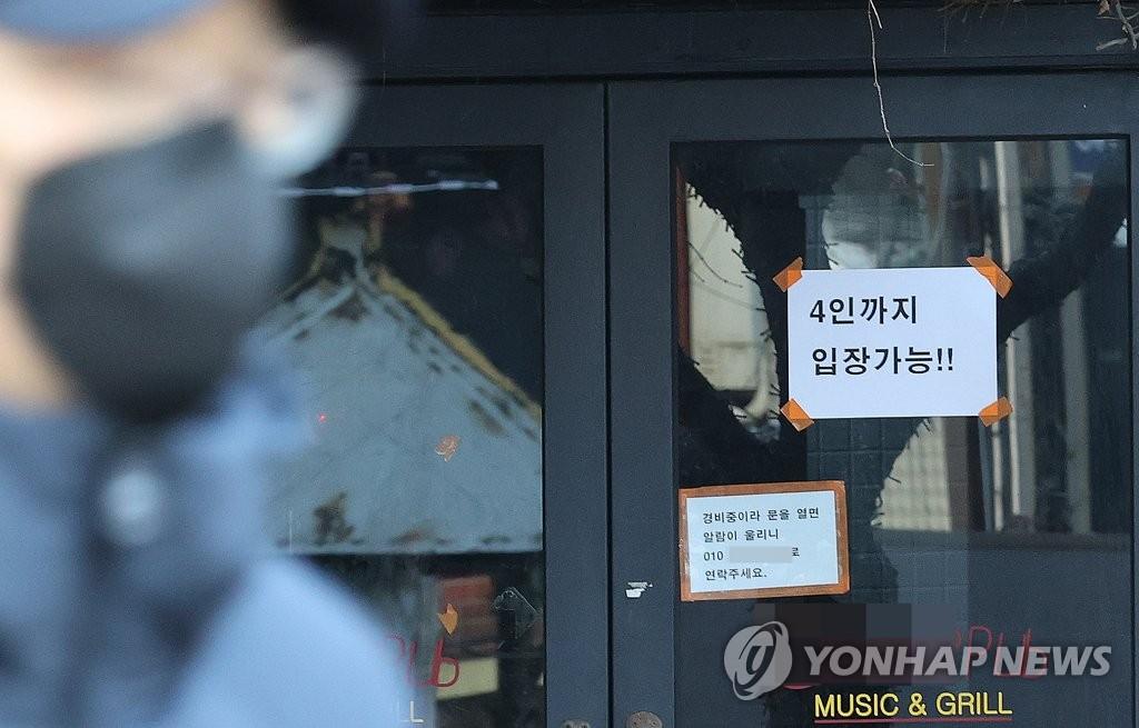1月17日,首尔麻浦区一家餐厅张贴着只准4人一起入堂就餐的告示。 韩联社