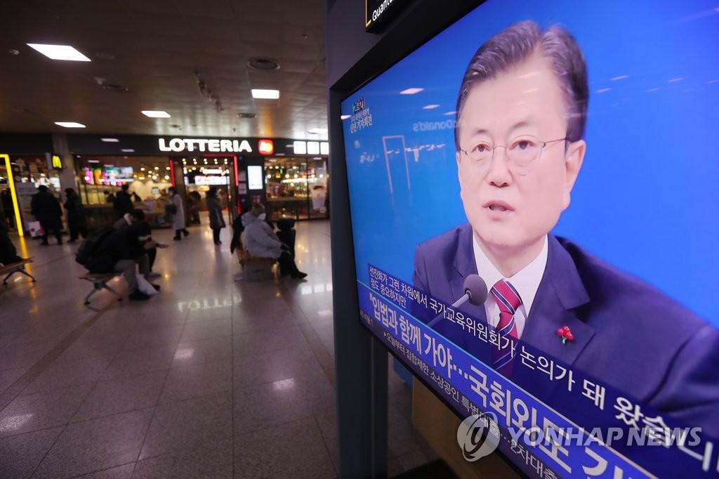 1月18日,在首尔站的候车大厅,正在播放文在寅新年记者会实况转播。 韩联社