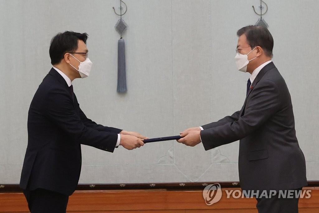 1月21日上午,在青瓦台,韩国总统文在寅(右)向高级公职人员犯罪调查处首任处长金镇煜授予任命书。 韩联社