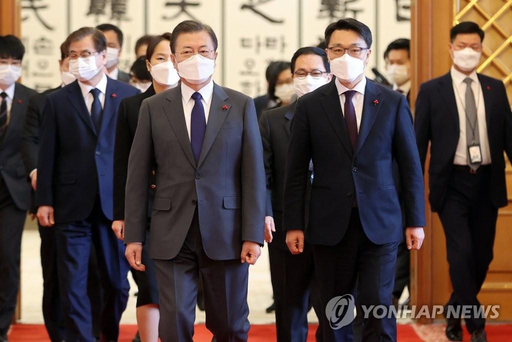 1月21日上午,在青瓦台,韩国总统文在寅(左)与高级公职人员犯罪调查处首任处长金镇煜步入会场。 韩联社