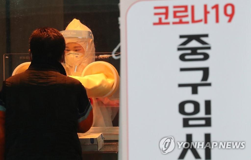资料图片:在首尔市一处筛查诊所,防疫人员对市民进行病毒检测。 韩联社