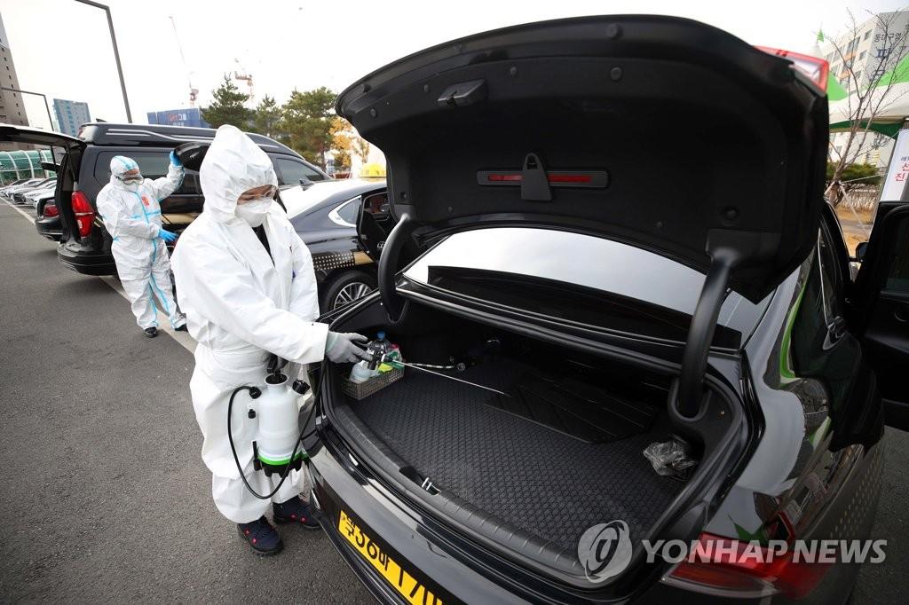 资料图片:接送入境人员的车辆接受消毒。 韩联社