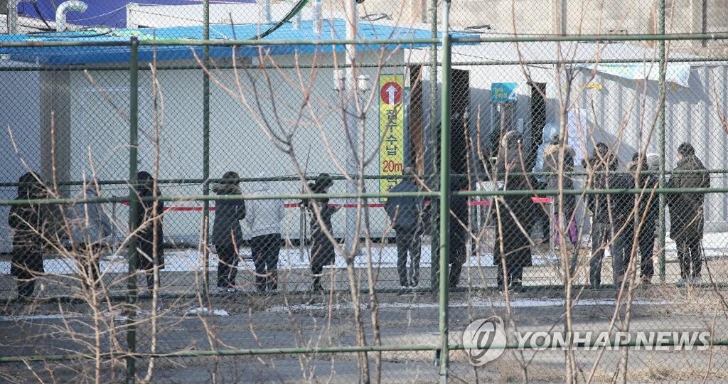 资料图片:2月17日上午,在设于顺天乡大学首尔附属医院的临时筛查诊所,市民们排队等候接受病毒检测。 韩联社