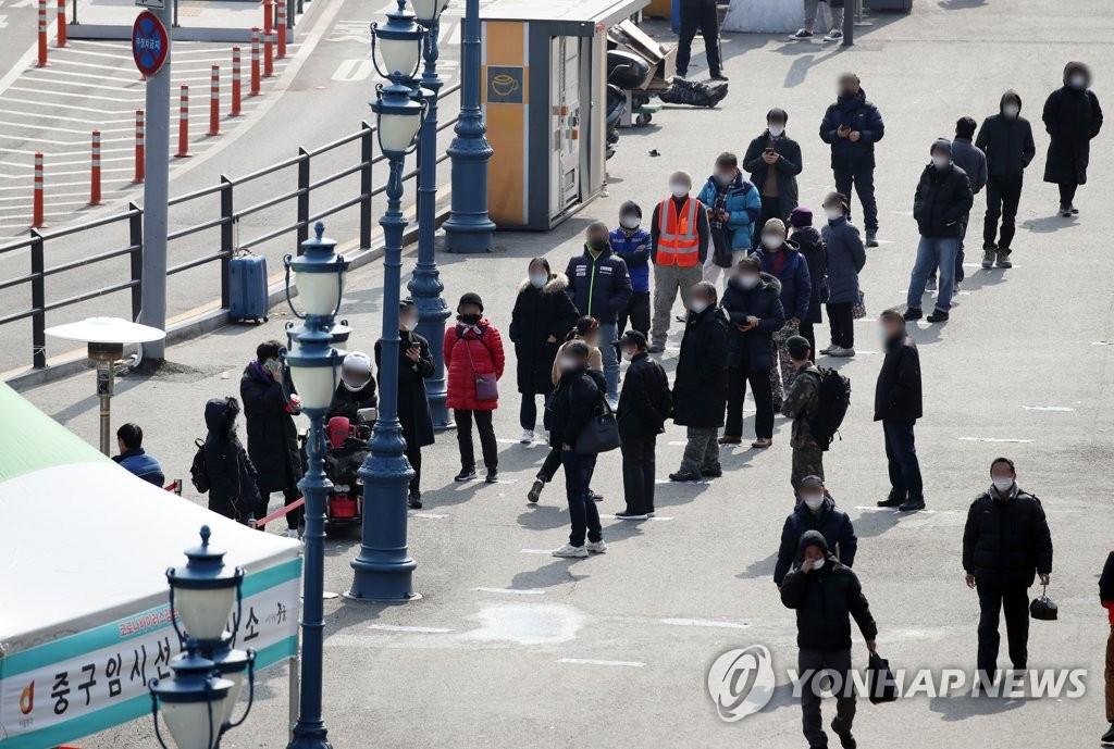 资料图片:2月19日,在设于首尔火车站广场的临时筛查诊所,市民等待接受病毒检测。 韩联社