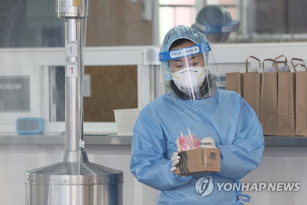 2月22日下午,在首尔市铜雀区卫生所,一名护士手持试剂盒准备进行核酸检测采样。 韩联社