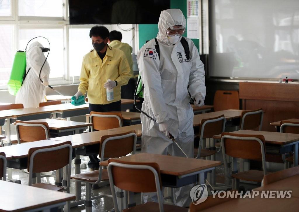 资料图片:2月23日,防疫人员为大邱市南区一高中的教室进行消毒消杀工作。 韩联社