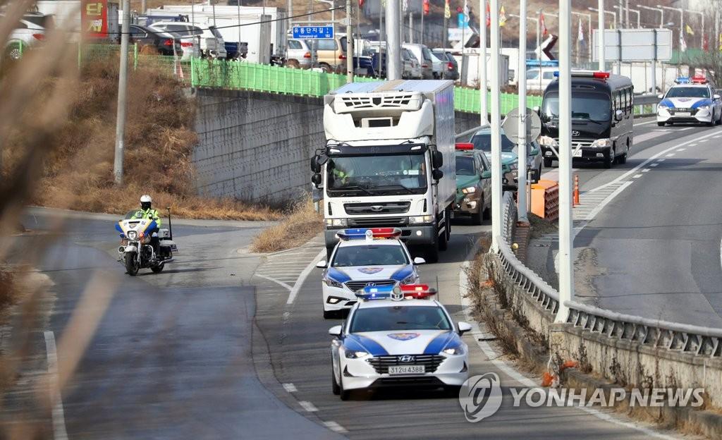 2月24日,一辆装载阿斯利康新冠疫苗的运送车辆在警车的护送下前往位于京畿道利川市的物流中心。 韩联社