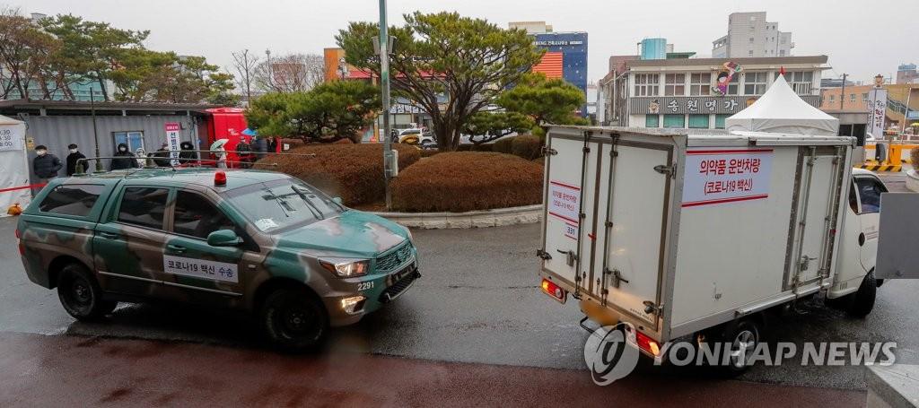 2月25日,在光州市一家卫生站前,一辆装有新冠疫苗的冷链运输车在警车的护送下抵达卫生站。 韩联社