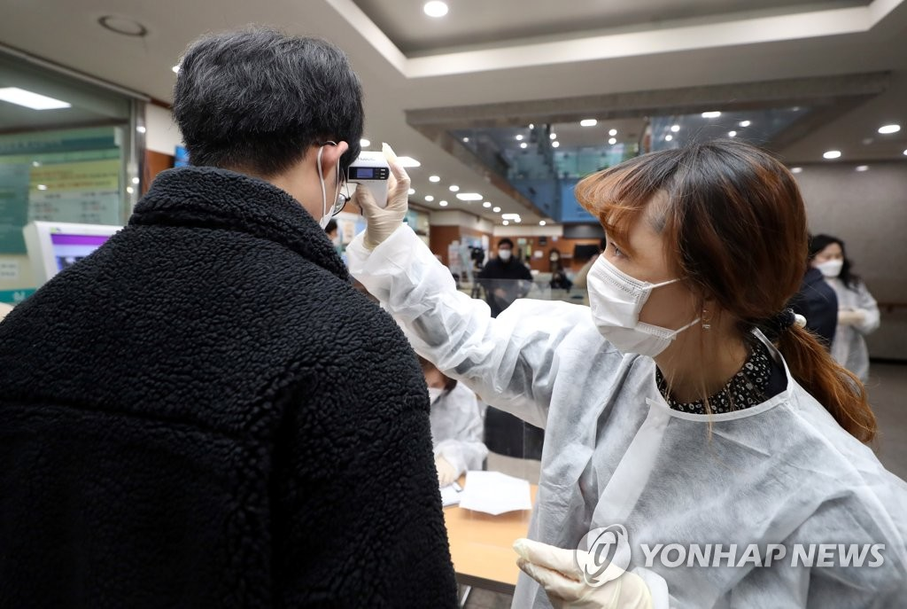 2月26日上午,在仁川市富平区卫生所,工作人员正在为预防接种者测体温。 韩联社