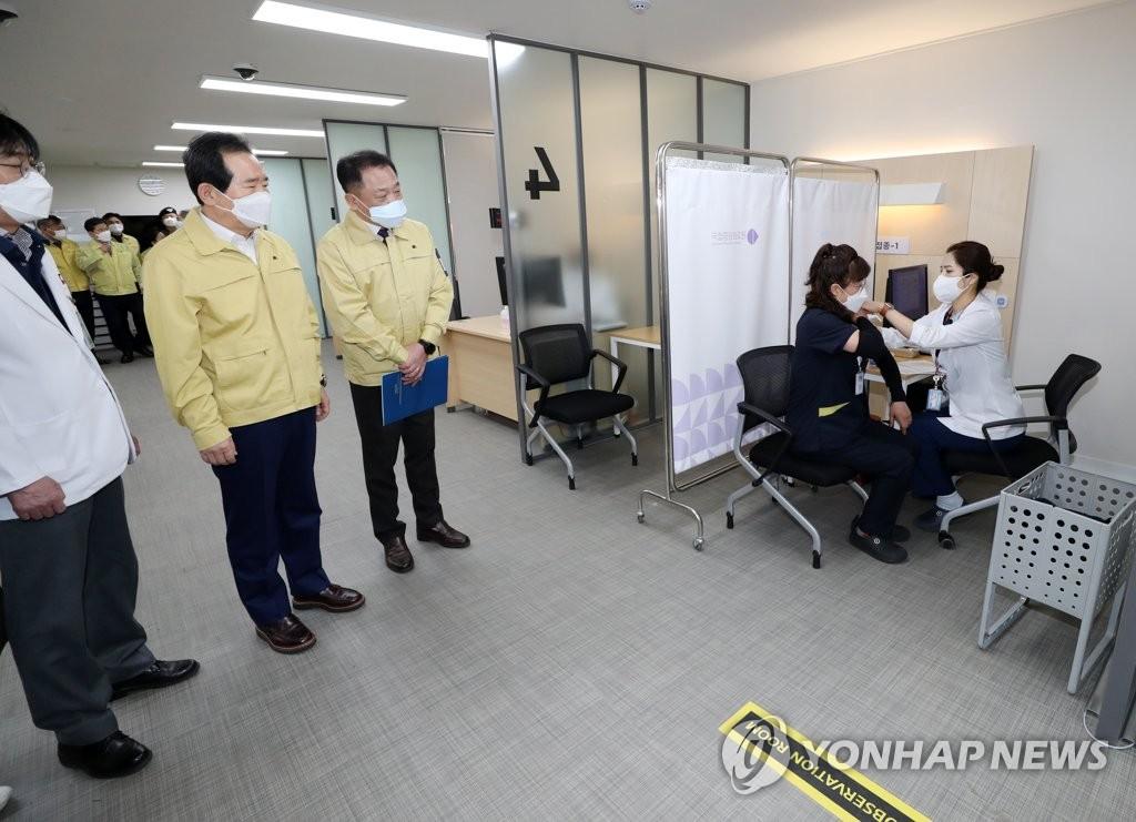2月27日,韩国务总理丁世均(左二)视察接种现场。 韩联社