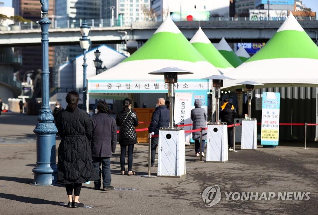 资料图片:在一处筛查诊所,市民排队侯检。 韩联社