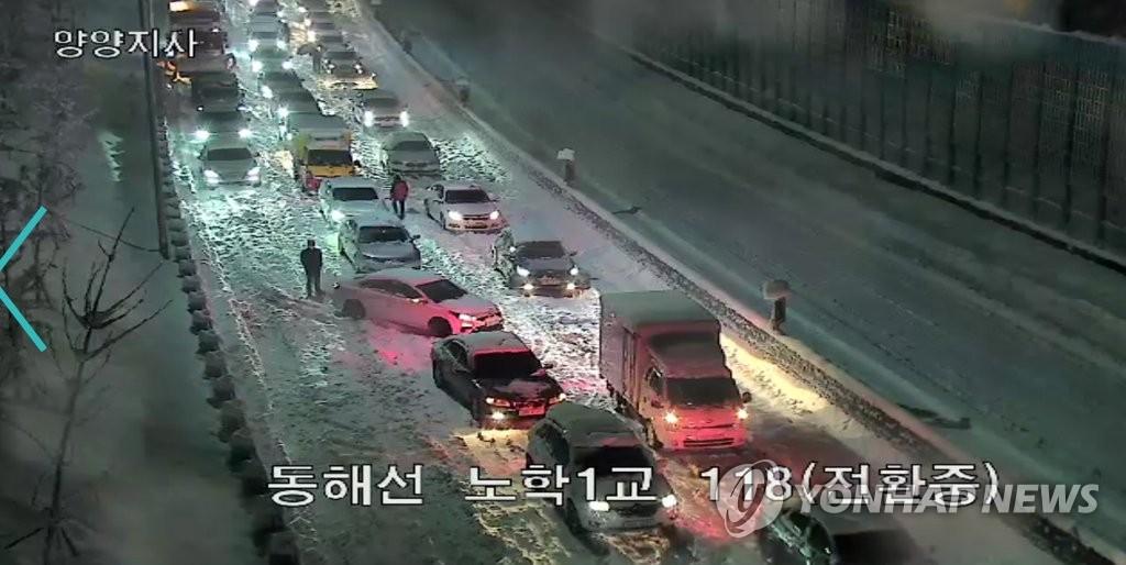 资料图片:3月1日,东海高速公路附近的车辆被困雪中。 韩国道路公社监控视频截图(图片严禁转载复制)