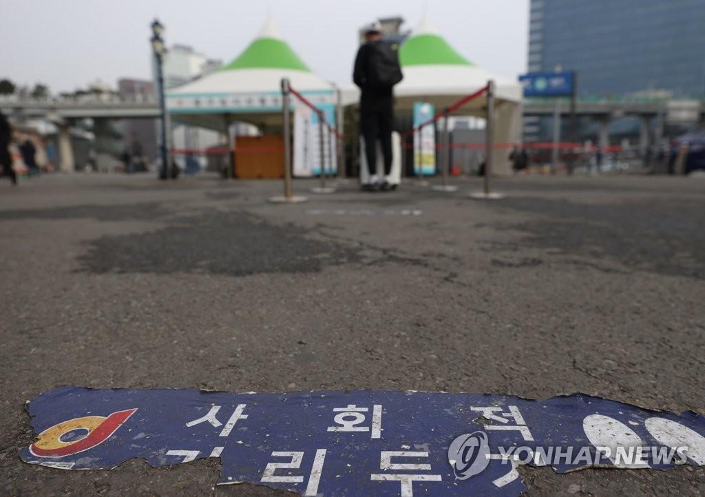 资料图片:在一处临时筛查诊所前,提醒人们保持社交距离的贴纸贴在地上。 韩联社