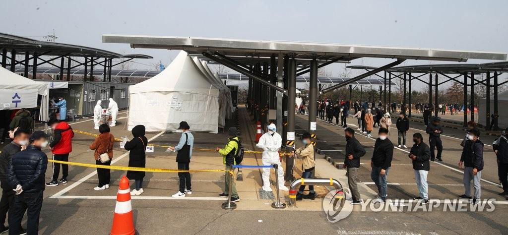资料图片:3月14日,在位于京畿道华城市的一处筛查诊所,外籍劳工排队候检。 韩联社