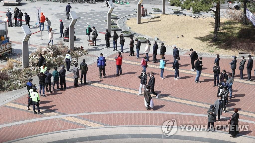 资料图片:在筛查诊所前排队待检的市民 韩联社