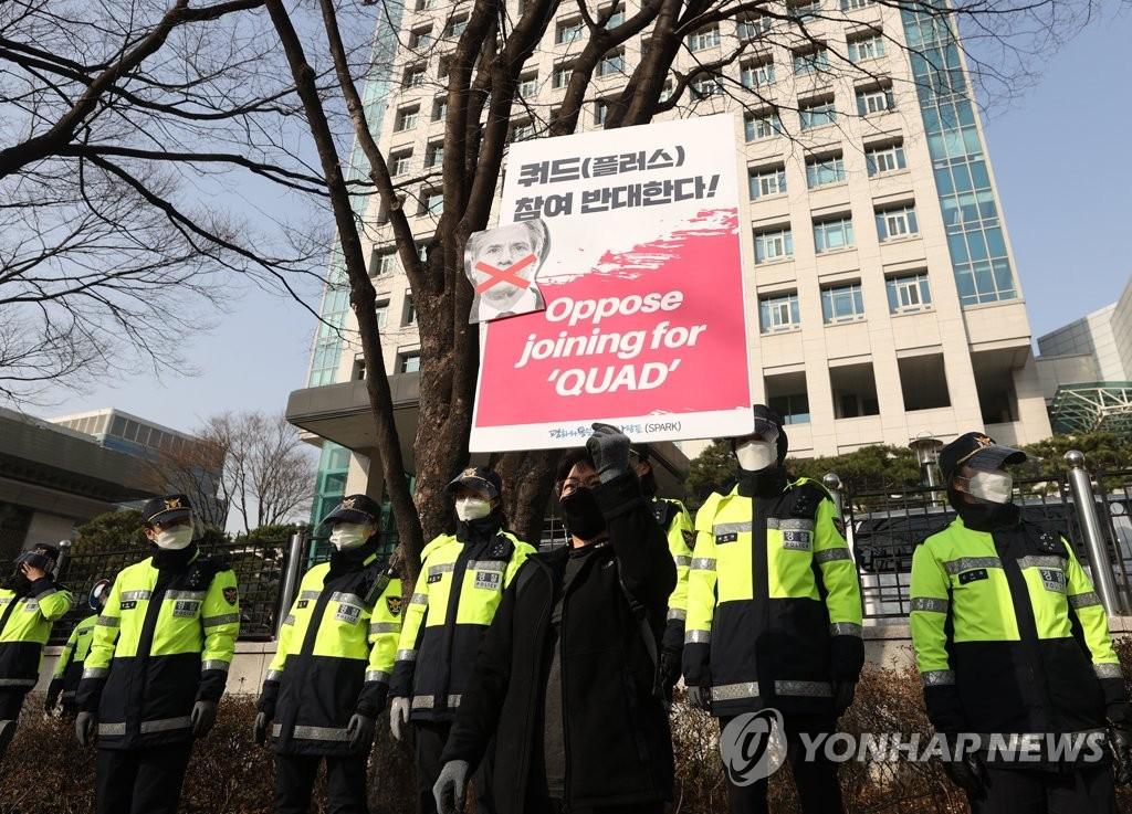 资料图片:3月18日,在外交部办公楼前,反对韩国加入四国集团的公民团体成员正在举牌抗议。 韩联社
