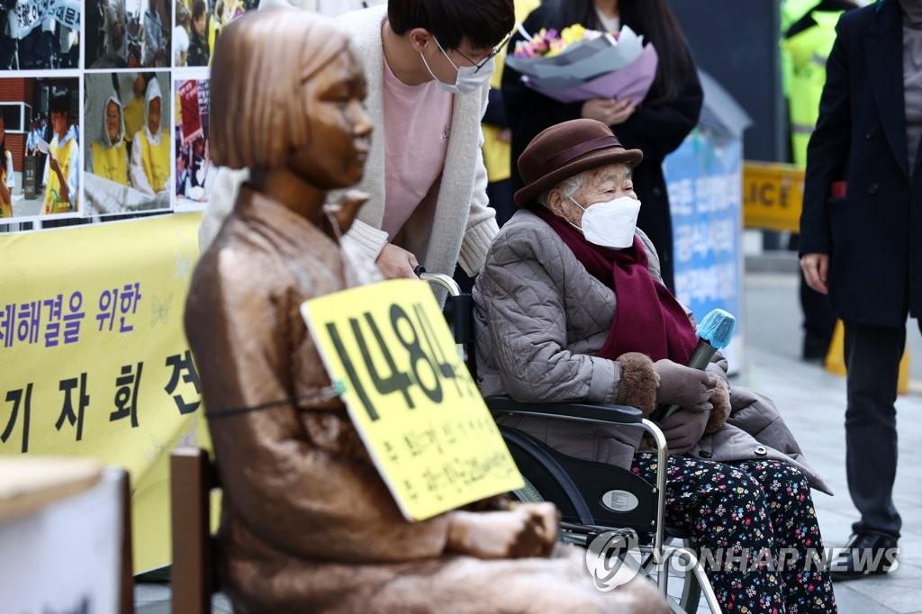 """资料图片:3月24日,在首尔日本驻韩大使馆旧址前,一名慰安妇受害人出席敦促日方解决慰安妇问题的""""周三集会""""。 韩联社"""