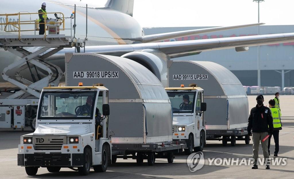 3月31日上午,韩国政府采购的辉瑞新冠疫苗中第二批25万人份运抵仁川国际机场。图为工作人员从联合包裹公司(UPS)货运航班上卸货。 韩联社