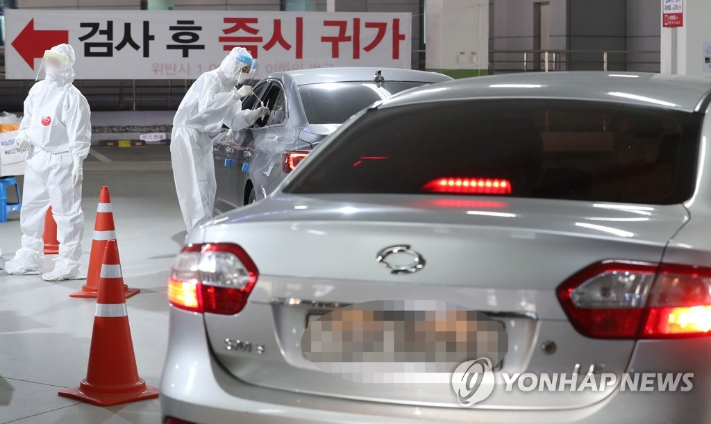 资料图片:3月31日,在世宗市,市民们免下车受检。 韩联社
