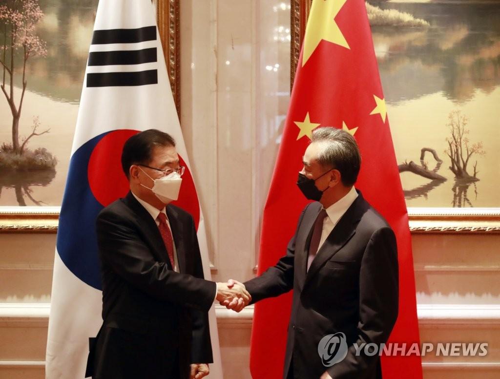 4月3日,在厦门海悦山庄酒店,韩国外交部长官郑义溶(左)同中国国务委员兼外交部长王毅在会谈前握手致意。 韩联社