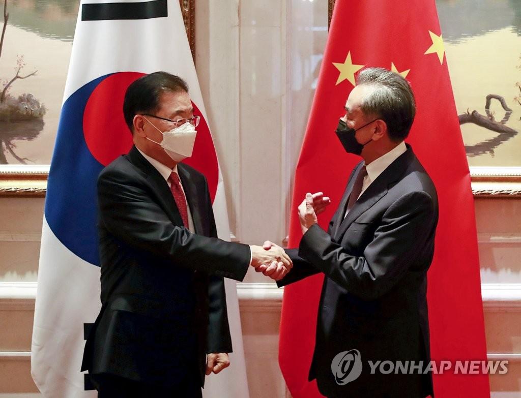 资料图片:4月3日,在中国厦门,韩国外交部长官郑义溶(左)与中国国务委员兼外交部长王毅握手致意。 韩联社